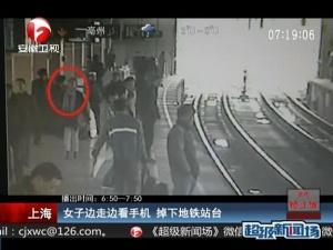 上海:女子边走边看手机 掉下地铁站台