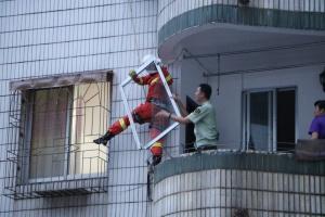 破损玻璃窗掉落四楼窗户雨棚 消防排险情(组图)