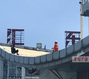 任性男子爬汽车站楼顶暴晒 消防员搭云梯救下(图)