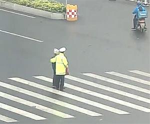老人过街到一半时红灯亮起进退两难 交警伸出援手