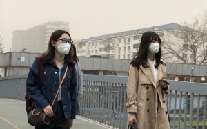 北京遭遇明显沙尘天气 天空昏黄行人掩面前行