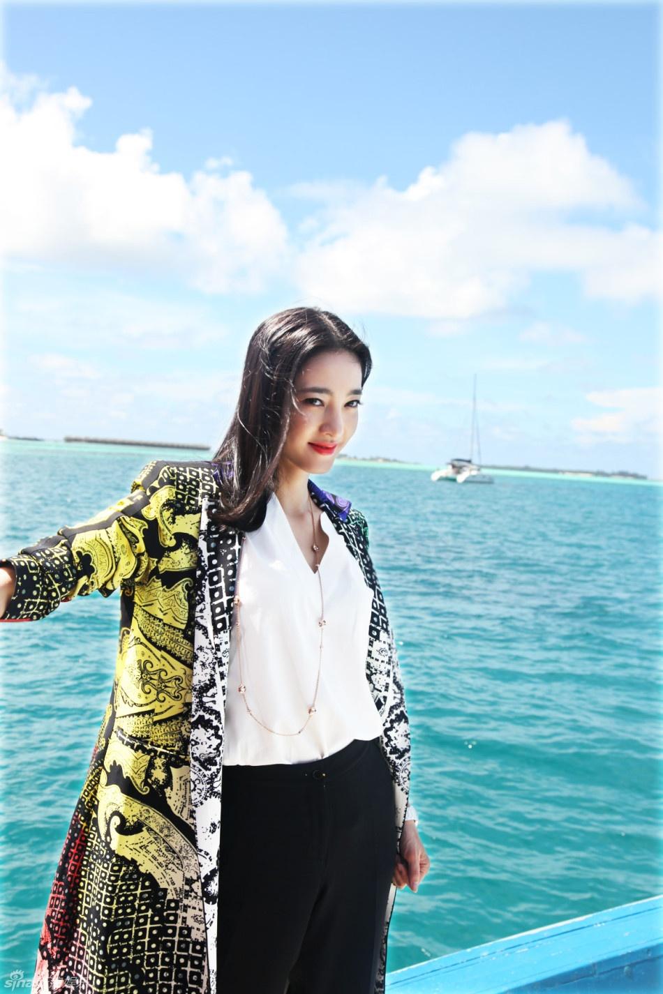广阔的海洋背景下,王丽坤身穿黑白二色的衬衫加长裤,搭配五色晕染印花