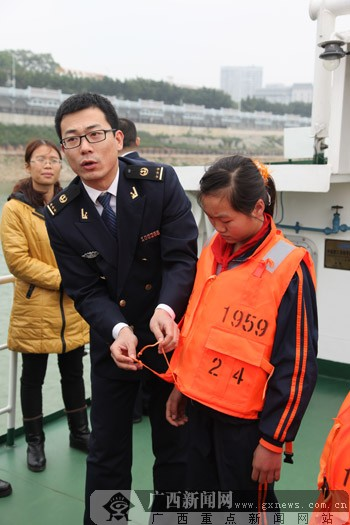 海事执法人员讲解救生衣的穿戴方法.