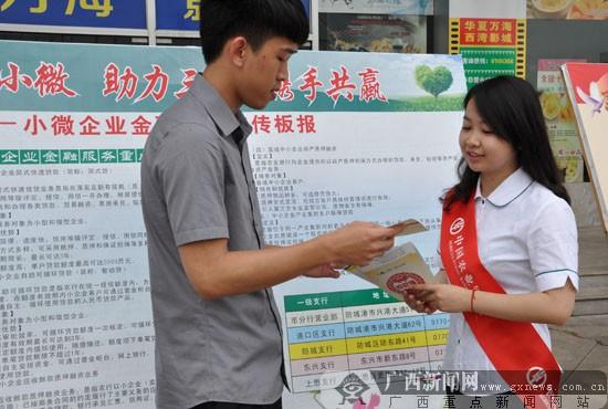 图为该行员工在宣传展板前向市民介绍小微企业相关政