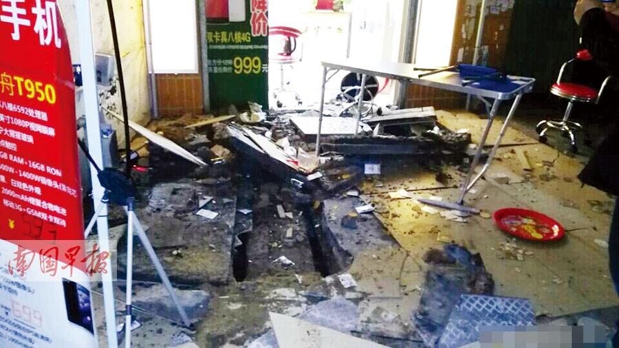 图为下水道爆炸发生后,沿街铺面的地板被炸开.