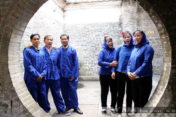 身着蓝衣壮传统服饰的村民欢唱壮歌迎宾客