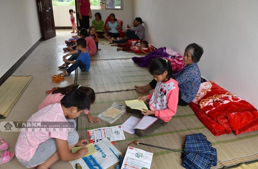 镇安置点,几名小学生在家长照看下做作业.广西新闻网通讯员 廖光