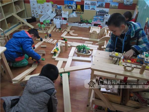 南宁市第五幼儿园大二班在开展挖地洞游戏。 图片由学校提供 游戏之乐溢满课堂 生活要亲身体验 怎么让孩子轻松地融入自主建构和社会建构的学习中?南宁市第五幼儿园大二班很有自己的一套办法。根据教育目标和幼儿发展水平,老师有目的地对班级的游戏活动区域作出规划和布局,创设出多样化的活动环境,投放活动材料。孩子们可以根据自己的能力和兴趣,在室内小型建构、户外大型建构和沙池中的沙水混合建构等游戏中摆弄操作活动材料,进行自主学习。 幼儿处于人生发展的起始阶段,4所幼儿园推荐的班级注重幼儿园本身的特性,根据幼儿的学习特点