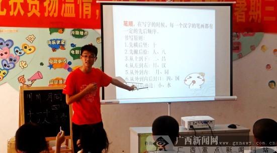 孩子们讲授写字的笔顺.通讯员供图-广西民大文学院送文化下乡 关