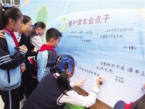 """滨湖路小学的同学们将为爱护免费循环使用课本想出的""""金点子""""写在背板图片"""