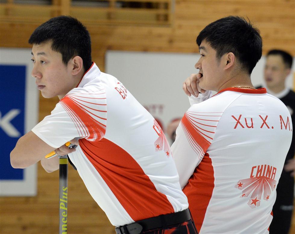 2月21日,中国队选手巴德鑫(左)与徐晓明观看对手投壶。 当日,在第八届亚冬会男子冰壶循环赛中,中国队以8比3战胜韩国队。新华社记者马平摄