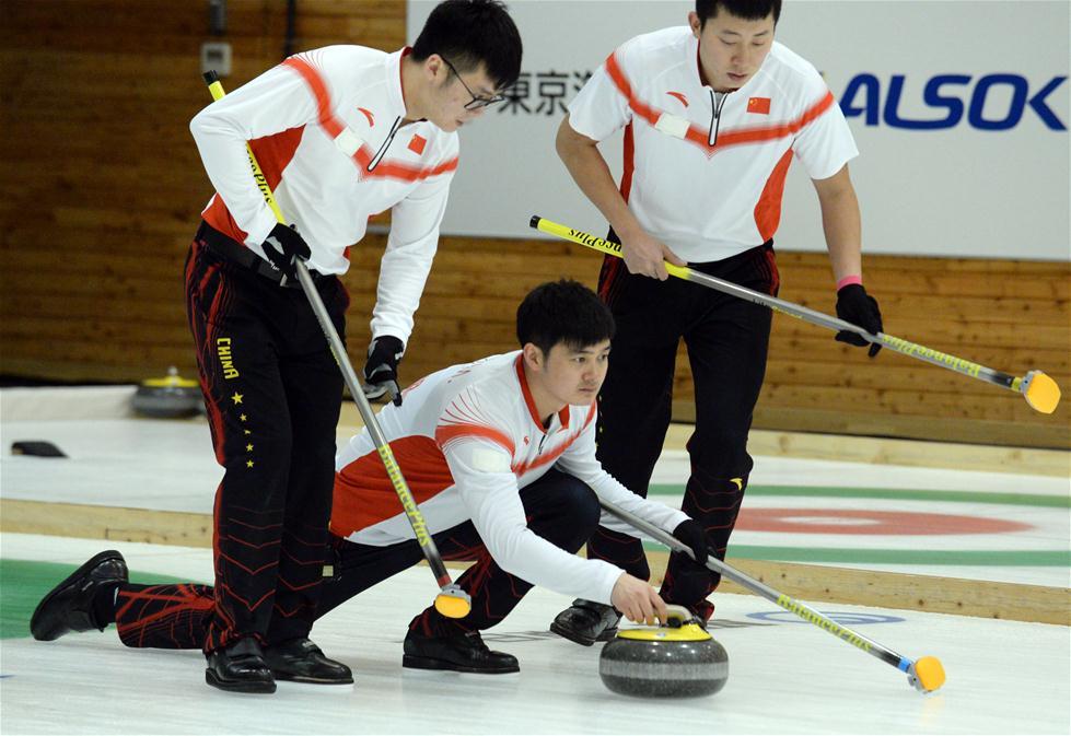 2月21日,中国队选手徐晓明(中)在比赛中投掷冰壶。 当日,在第八届亚冬会男子冰壶循环赛中,中国队以8比3战胜韩国队。新华社记者马平摄