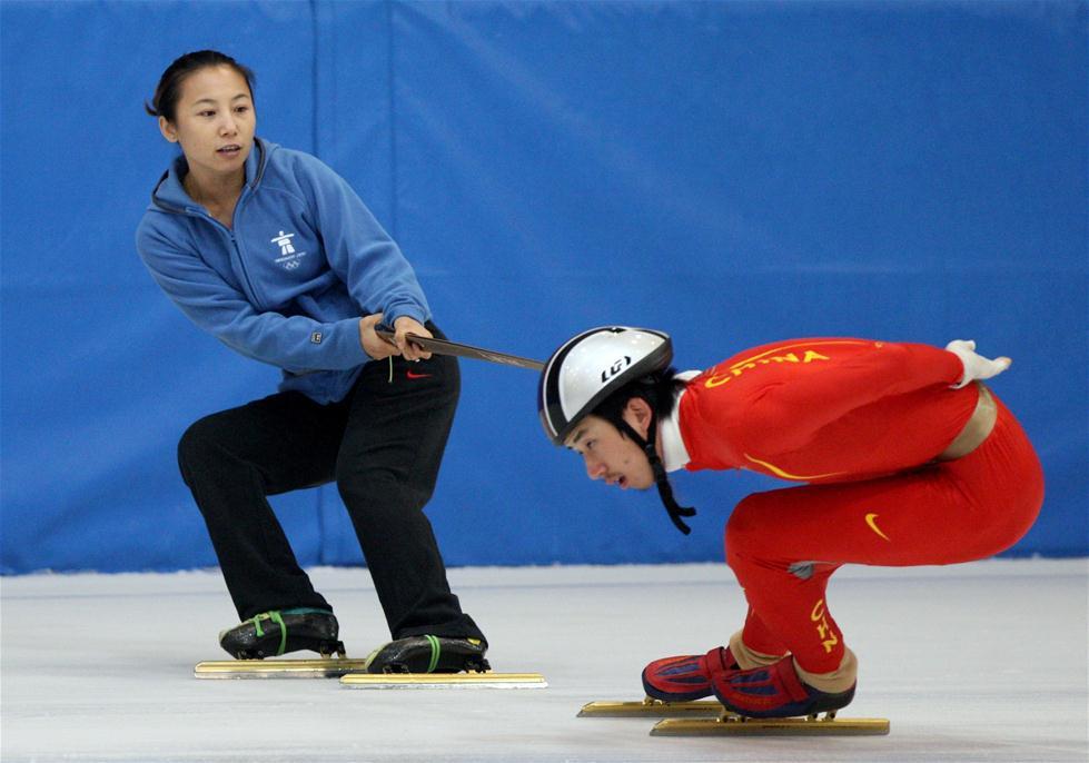 """在职业体坛长久以来男运动员的教练基本由男性""""统治""""。如今,越来越多的女性教练闯入这一领域,撑起了属于自己的半边天。图为2010年8月18日,中国短道速滑队主教练李琰(左)在对男队员杨劲进行技术指导。 新华社发"""