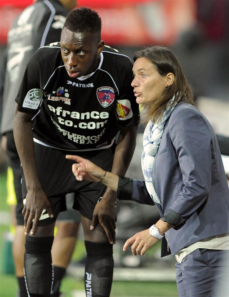 """在职业体坛长久以来男运动员的教练基本由男性""""统治""""。如今,越来越多的女性教练闯入这一领域,撑起了属于自己的半边天。图为2014年8月4日,克莱蒙特队主教练迪亚克尔(右)在法国足球乙级联赛中为球员布置战术。迪亚克尔是法国足球史上首位执教男子职业足球队出战联赛的女性主教练。新华社发"""