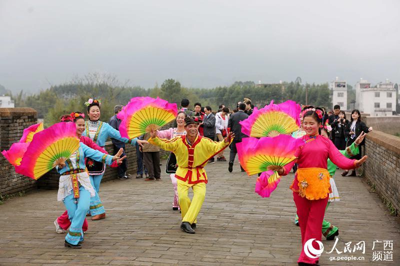 3月13日,在广西贺州市八步区贺街镇具有2000余年历史的临贺故城古城墙上,文艺队员在演唱彩调经典曲目《探花》选段(谭凯兴/摄)
