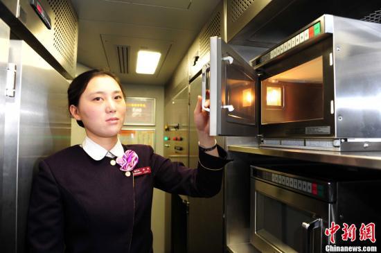图为乘务员展示哈大线车上配备的微波炉。<a target='_blank' href='http://www.chinanews.com/'></table>中新社</a>发 于海洋 摄