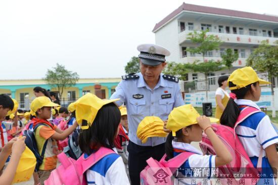 """钦州交警为小学生发放交通安全""""小黄帽"""""""