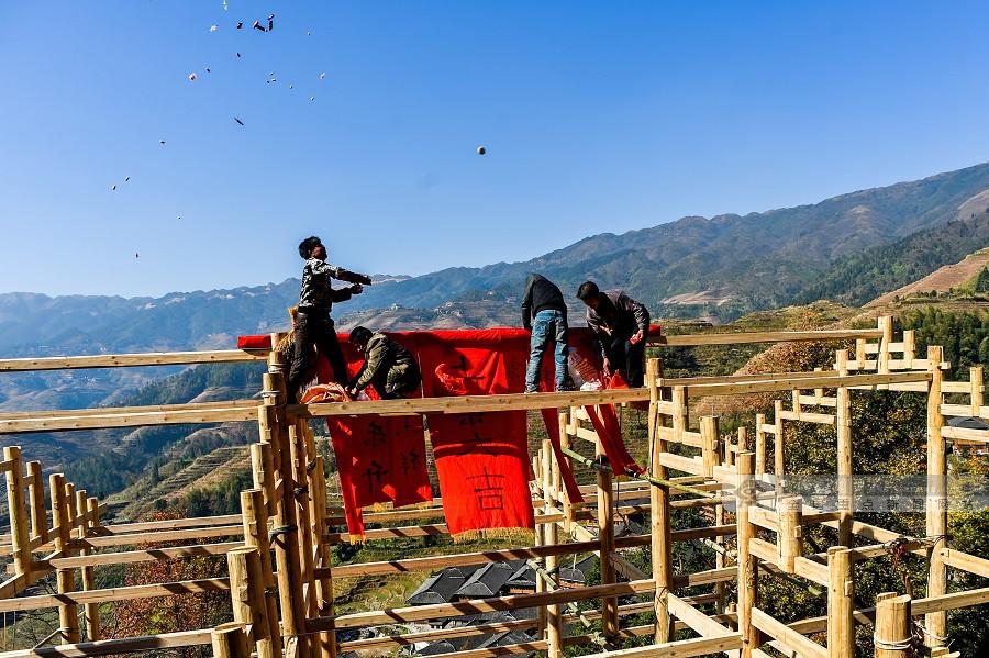 建吊脚楼是一个浩大的木结构建筑拼装工程,没有建房图纸,全凭一根杖杆