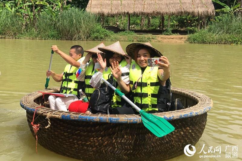 6月25日,广西大新县老木棉景区,游客们正在体验乘坐越南簸箕船