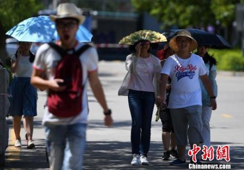 7月13日,厦门市民行走在热浪滚滚的路面上。 张斌 摄