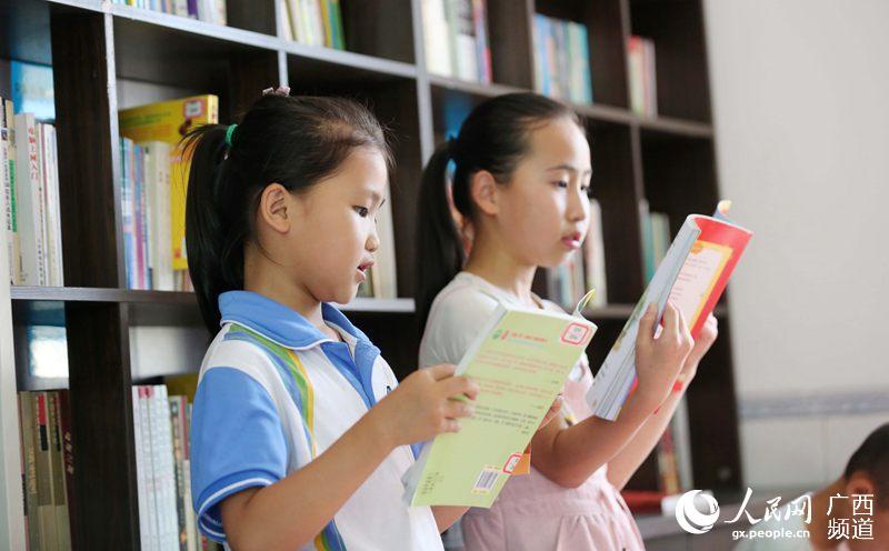 7月13日,广西柳州市融安县泗顶镇三坡村,留守儿童在农家书屋里看书(谭凯兴/摄)