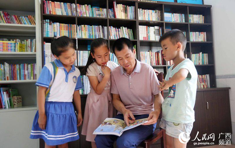 7月13日,广西柳州市融安县泗顶镇三坡村农家书屋,一名老师在辅导学生阅读书籍(谭凯兴/摄)