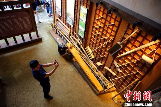 一名游客在村史馆内拍照。 朱柳融 摄