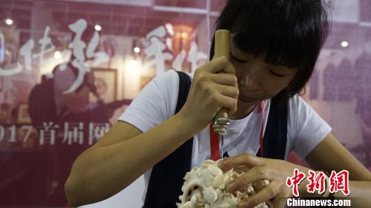 骨雕手艺人黄秋平展示骨雕制作技艺。 朱延生 摄