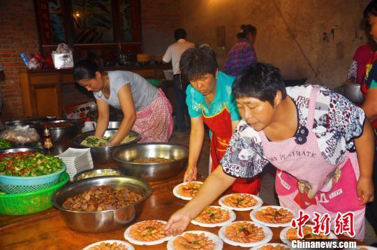 村民在准备菜肴。 张强 摄