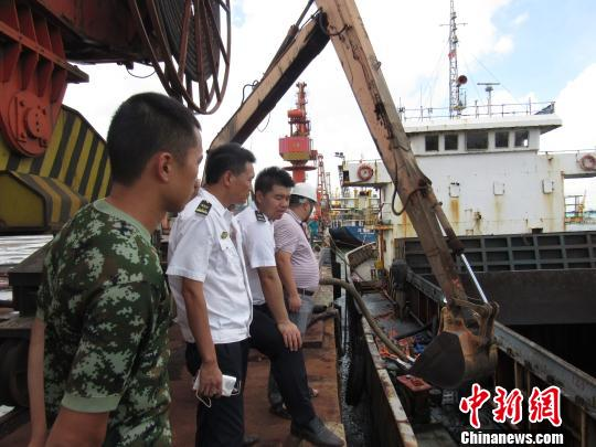 图为利用抓斗对船舱内进水和钛矿进行抢卸。 李有国 摄