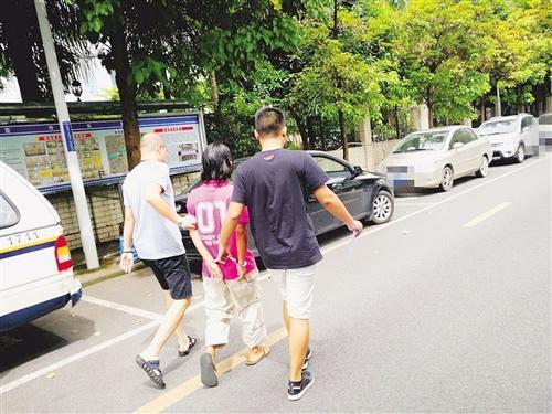 男子(中)被警方带去指认现场 本报记者 潘国武 摄