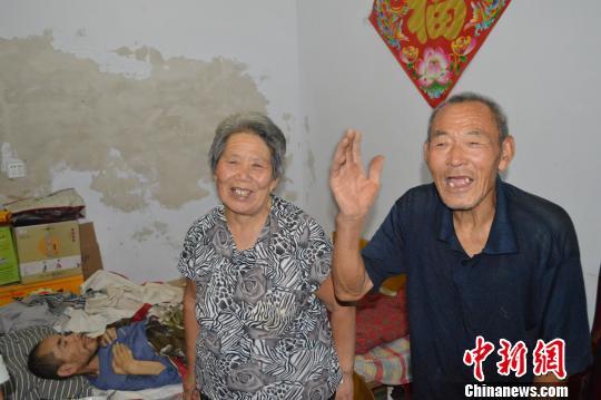 77岁老人潘明玉和72岁的老伴董荣端,37年来不离不弃地照顾着丧失行动能力的儿子潘志通。 谢翠玲 摄