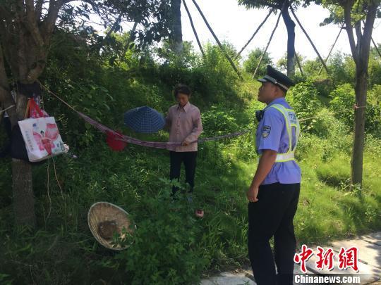 图为陈佳益劝阻在路边树木上挂吊床的路人 林馨 摄