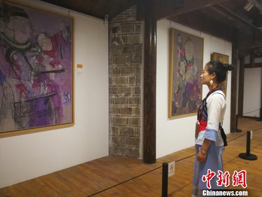 一位姑娘正在观看展出的作品。 主办方供图