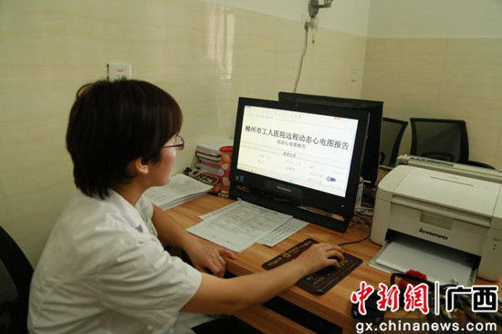 图为柳州市阳和社区医院陈医生正在查看由柳州市工人医院远程诊断出具的动态心电图报告。