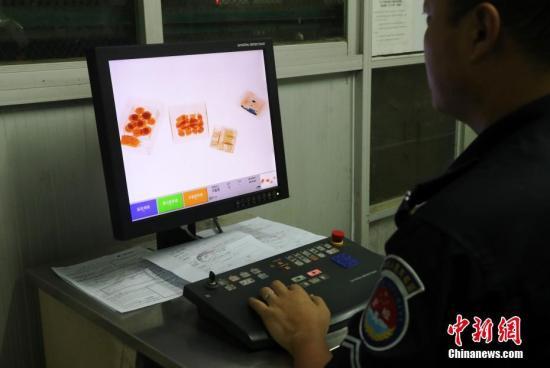 资料图:安检人员对货邮进行x光检查并填写申报单。<a target='_blank' href='http://www.chinanews.com/'></table>中新社</a>记者 刘占昆 摄