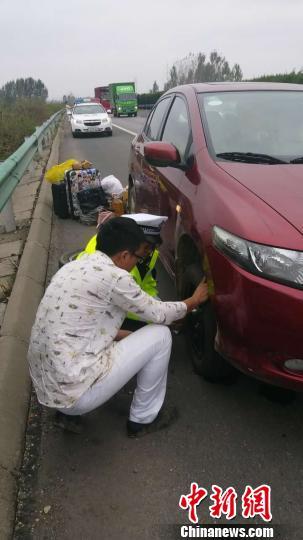 图为河南高速交警在应急车道上帮助爆胎的小客车换胎。河南高速交警供图