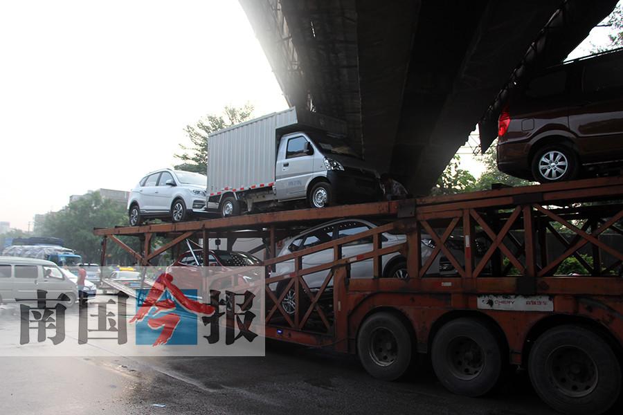"""装得太高!大型货车""""背""""小车被卡桥底动弹不得(图)"""