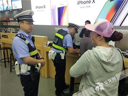 一名民警与消费者沟通,另一名民警向手机店工作人员小霍了解情况。记者 张勇 摄
