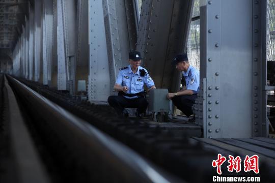 图为,黄小勇与战友一道检查线路设施设备 胡金力 摄