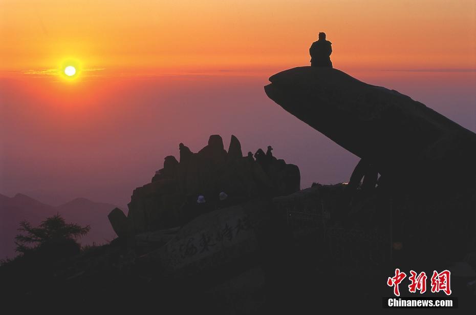 """泰山位于山东省中部,主峰玉皇顶海拔1545米,气势雄伟磅礴,有""""五岳之首""""、""""五岳之长""""、""""天下第一山""""之称。图为游客在泰山上看日出。 谢光辉 摄 图片来源:CTPphoto"""
