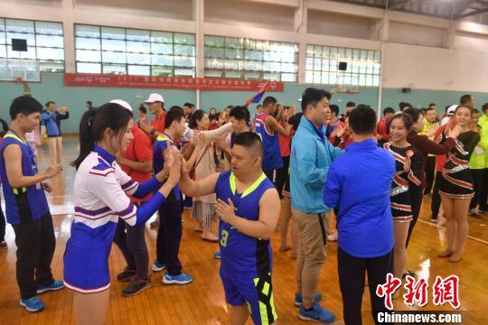 赛前,运动员与来宾、拉拉队队员一起跳舞。 吕明 摄