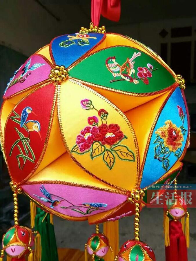 黄肖琴的作品。 8岁时 她就会做绣球了 黄肖琴出生于广西百色靖西县旧州街,她的父亲曾是民间手艺人,会制作木雕、舞龙的龙头等手工艺品。 黄肖琴的家乡有制作绣球的传统。在她小的时候,当地就有很多人会做绣球。耳濡目染下,黄肖琴8岁那年就会自己制作绣球了。因为父亲常常教她画画,所以她可以在绣片上画出各种图案。 20世纪80年代初,因为家里经济困难,黄肖琴便绣些背带之类的物品,拿到集市上卖。那个时候,一条背带要绣4天左右时间,能卖3元钱。黄肖琴回忆说,在那个年代,她白天要在地里干活,晚上还要抽空做绣球、刺绣背带,