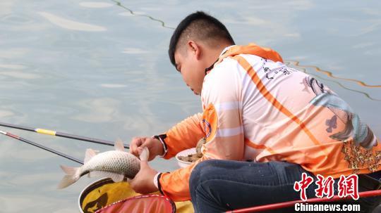 图为一名选手在比赛中将收获的鱼小心地放入篮子里。 黄仲 摄