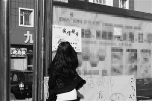 """光华学院电气信息学院的大学生制作的""""诚信硬币""""悬挂在361路终点站。 袁迪 摄"""