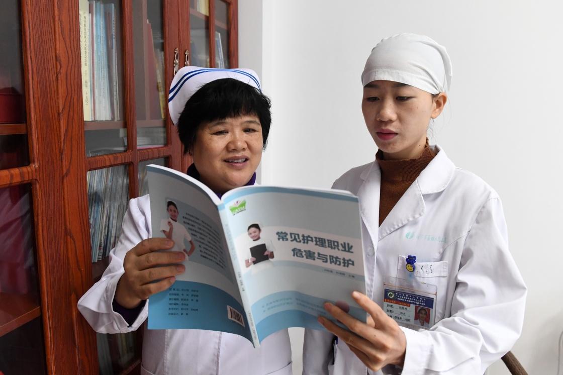 亚洲护士无码_郭应玲(右)向护士长杜丽群请教护理常识
