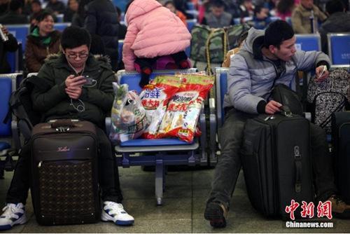 """资料图:铁路青岛站候车室内,玩手机的""""低头族""""随处可见。<a target='_blank' href='http://www.chinanews.com/'></table>中新社</a>发 徐崇德 摄"""