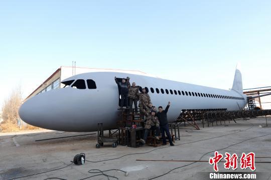 """辽宁铁岭6位农民历时一年制成""""空客A320"""",完工前夕在飞机前合影。 杨也迅 摄"""