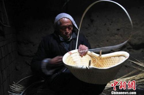 柳编艺人在编织柳编作品。 张鹏翔 摄