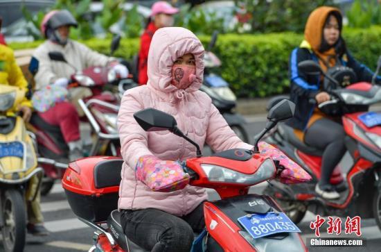 """12月20日,海口民众""""全副武装""""出行抵御冷空气。 <a target='_blank'  data-cke-saved-href='http://www.chinanews.com/' href='http://www.chinanews.com/'></table>中新社</a>记者 骆云飞 摄"""